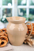 Jar of milk, tasty bagels and spikelets on table — Stock Photo