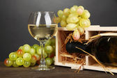 Wooden case with wine bottle, wineglass and grape on wooden table on grey background — Stock Photo