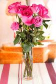 Krásné růžové růže ve váze na stole v místnosti pozadí — Stock fotografie