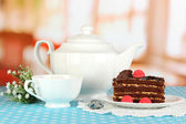 Teapot, cup of tea and delicious cake on room background — Stock Photo