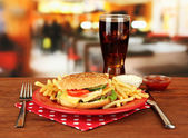 Tasty cheeseburger with fried potatoes and cold drink, on bright background — Stock Photo
