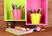 Colorful pencils in pails on shelves on wooden background — Stock Photo