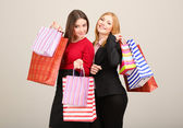 Iki kız arkadaş gri arka plan üzerinde alışveriş — Stok fotoğraf