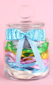 Glass jar containing various colored ribbons on pink background — Stock Photo