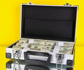 Suitcase with 100 dollar bills on yellow background — Stock Photo