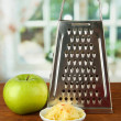 Metal grater and apple, on bright background - 图库照片