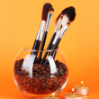 Glass bowl with coffee beans,brushes and candles on orange background — Stock Photo