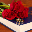 Wedding rings on bible with roses on wooden background — Stock Photo
