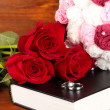 Wedding rings on bible with roses on wooden background — Stock Photo #23002976
