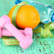 Orange with measuring tape, dumbbells and bottle of water, on color wooden background — Stock Photo