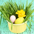 Easter eggs in bowl with grass on green wooden table close up - Stock Photo