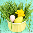 Easter eggs in bowl with grass on green wooden table close up - Stockfoto