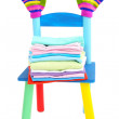 Small and colorful chair with baby clothes isolated on white — Stock Photo
