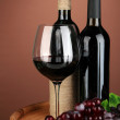 Composition of wine bottle, glass of red wine, grape on wooden barrel, on color background — Stock Photo #23003704