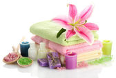 Towels with lily, aroma oil, candles, soap and sea salt isolated on white — Stock Photo