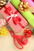 Rolls of Christmas wrapping paper with ribbons, bows on wooden background — Stock Photo