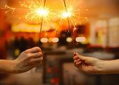 Beaux feux de bengale dans femme mains sur chambre backgroun — Photo
