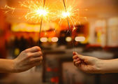 Beautiful sparklers in woman hands on room backgroun — Stock Photo