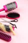 Comb brushes, hair and cutting shears, on pink background — Stock Photo