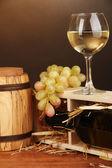 şarap şişesi, varil, bardağı ve üzüm kahverengi zemin üzerine ahşap masa üzerinde ahşap durumda — Stok fotoğraf