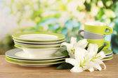 Empty plates and cups on wooden table on green background — Stock Photo