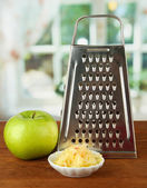 Metal grater and apple, on bright background — Stock Photo