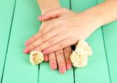 Kobieta ręce z różowy manicure i kwiaty, na tle drewniane kolor — Zdjęcie stockowe