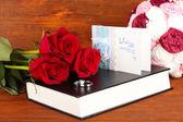 Anéis de casamento com rosas na bíblia sobre fundo de madeira — Fotografia Stock