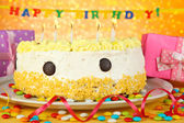 Happy birthday cake and gifts, on yellow background — Stock Photo