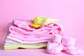 Pile of baby clothes on pink background — Stock Photo