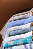 Men's shirts on hangers on brown background — Stock Photo