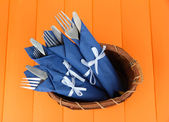 Forks and knives wrapped in blue paper napkins, in basket, on color wooden background — Stock Photo