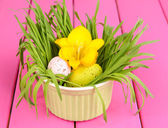 Easter eggs in bowl with grass on pink wooden table close up — Stock Photo