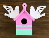Decorative nesting box with paper birds, on wooden background — Stock Photo