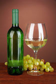 Composition of wine bottle, glass of white wine, grape on color background — Stock Photo