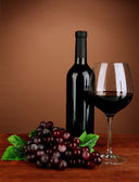 Composition of wine bottle, glass of red wine, grape on color background — Stock Photo