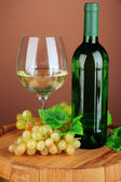 Composition of wine bottle, glass of white wine, grape on wooden barrel, on color background — Stock Photo