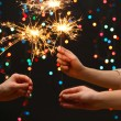 Beautiful sparklers in woman hands on garland backgroun — Stock Photo #23029028