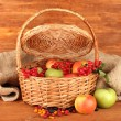 Crop of berries and fruits in a basket on wooden background close-up - Stock Photo