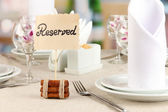 Reserved sign on restaurant table with empty dishes and glasses — Stock Photo