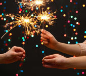 Beautiful sparklers in woman hands on garland backgroun — Stock Photo
