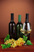 Composition of wine bottles, glass of white wine, grape on color background — Stock Photo