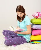 Hermosa joven con almohadas y libro en habitación — Foto de Stock
