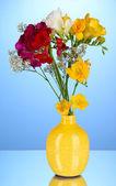 Schönen blumenstrauß aus freesien in vase auf blauem hintergrund — Stockfoto