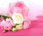 Ranunculus (persian buttercups) and gift, on pink wooden background — Stock Photo