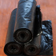 Plastic garbage bags on wooden background close-up - Stock Photo