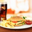 Tasty cheeseburger with fried potatoes and cold drink, on bright background — Stock Photo #23055320
