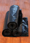 Plastic garbage bags on wooden background close-up — Stock Photo