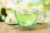 Transparent cup of green tea on bamboo mat, on nature background — Stock Photo