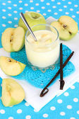Delicious yogurt in glass with apple on blue tablecloth — Stock Photo